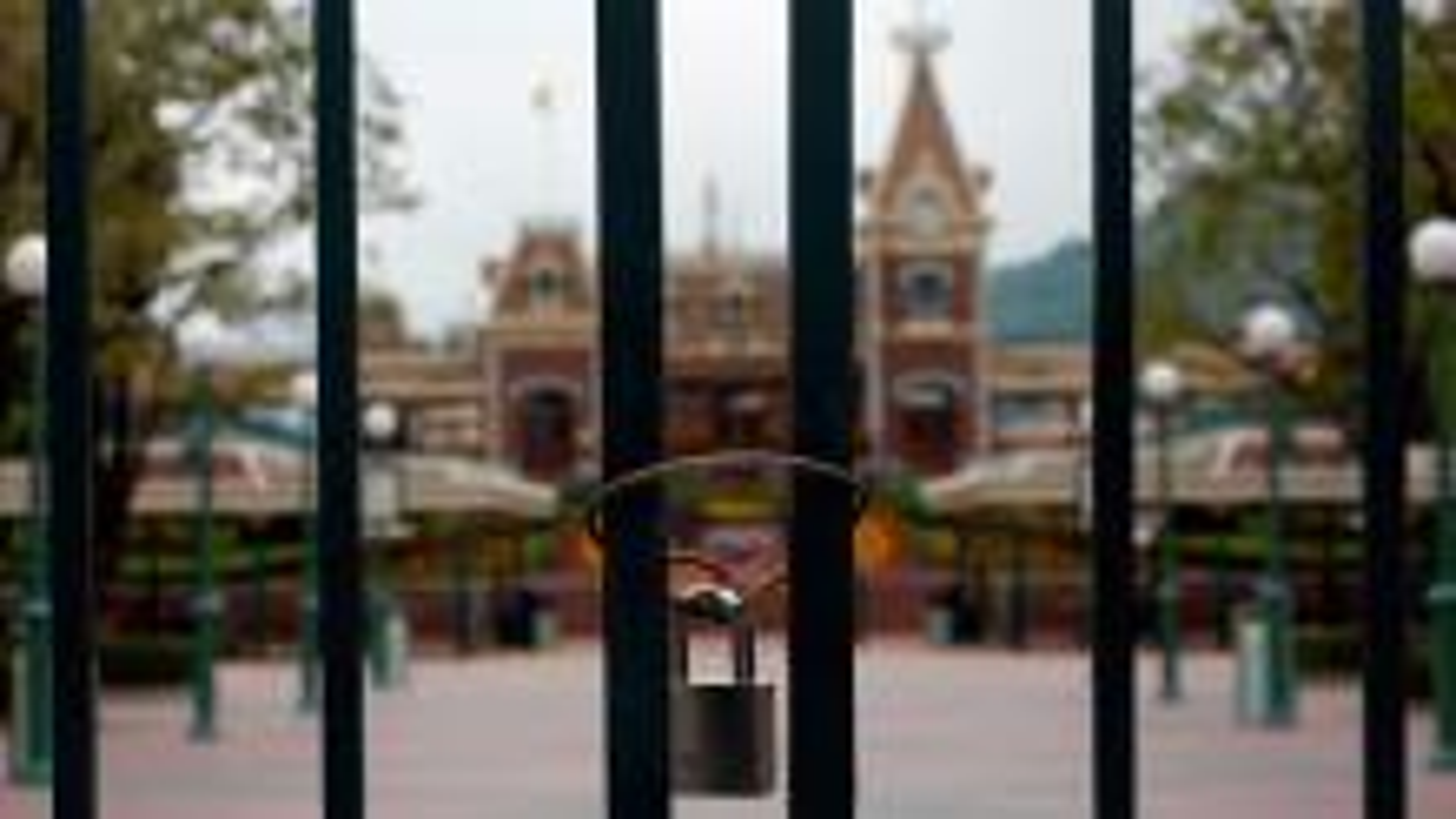 Hong Kong Disneyland is seen behind locked gates