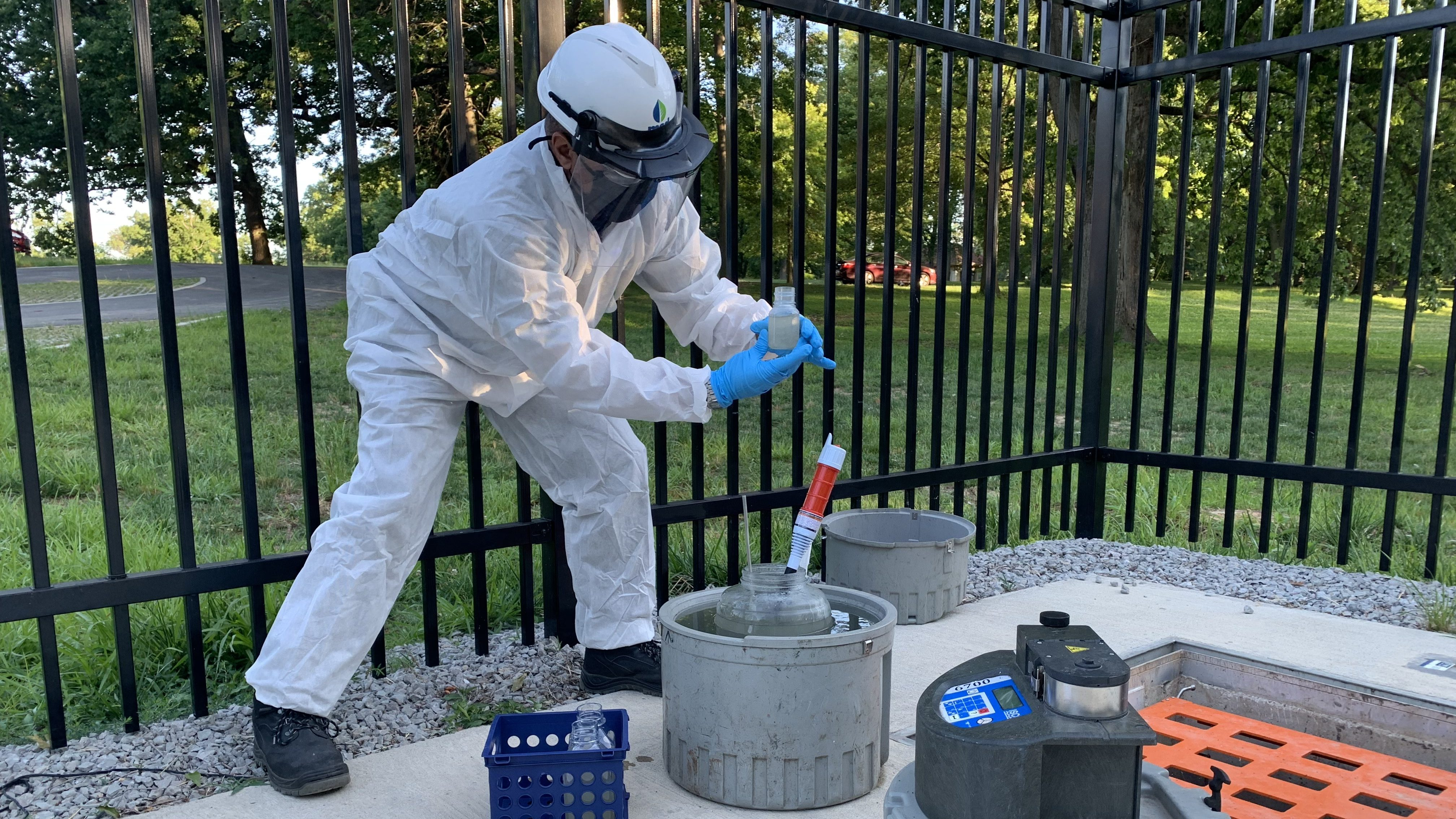A person in a personal protective gear suit holds a sample of wastewater collected from the sewer below