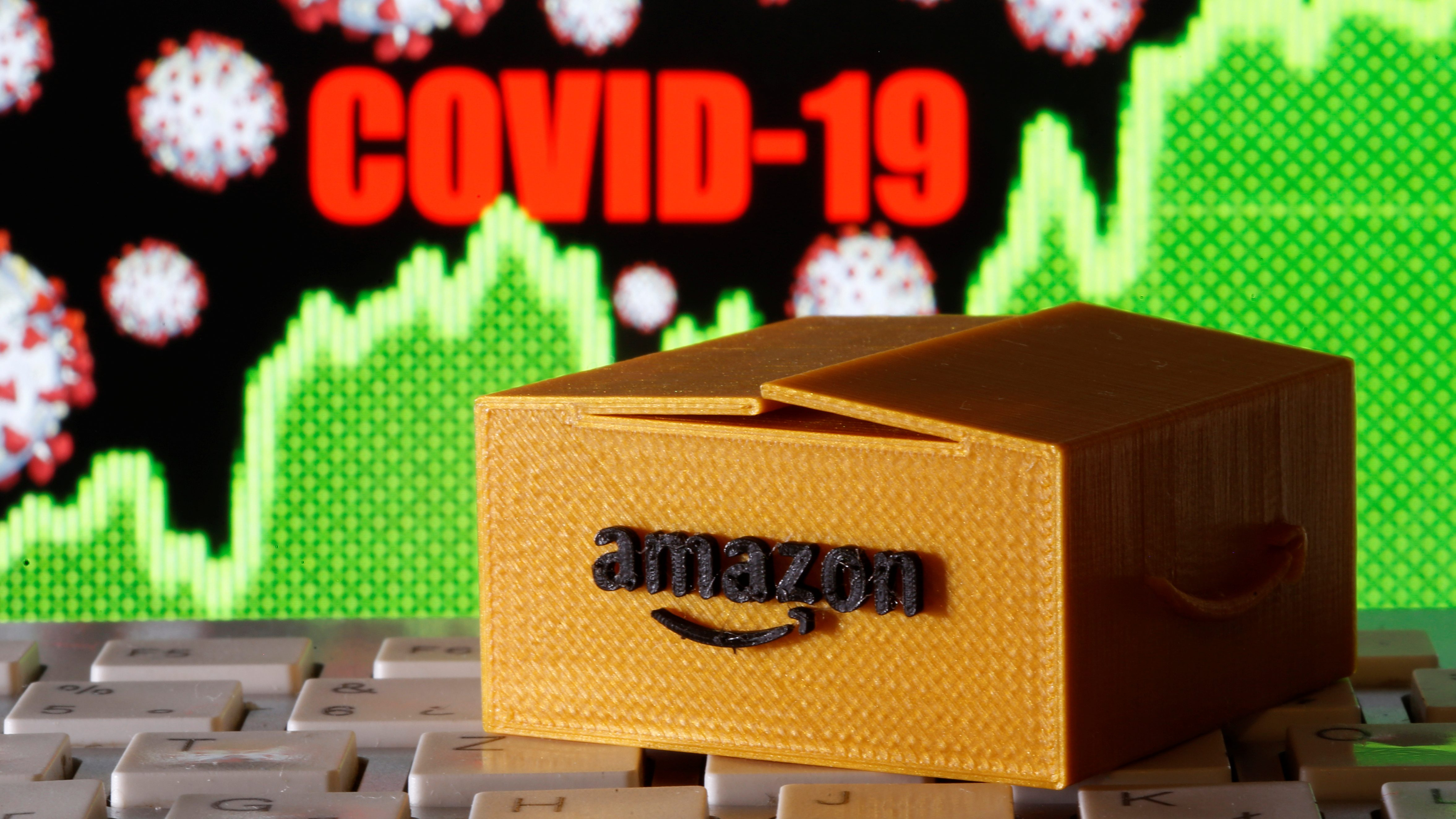 An Amazon box on top of a keyboard with a Covid-19 chart in the background.