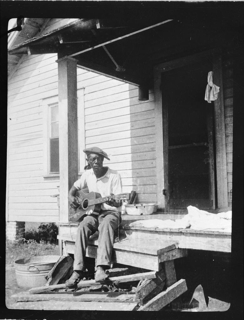 Photo of Bill Tatnall playing guitar on steps