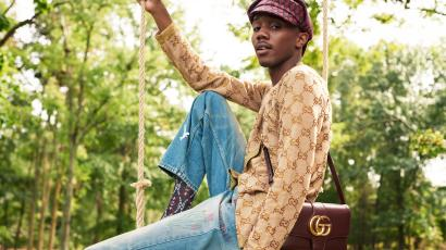 A male model decked out in Gucci sits casually on a swing