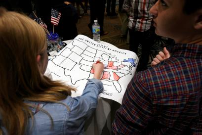 A girls colors an electoral map of the United States in either red or blue as returns are announced.