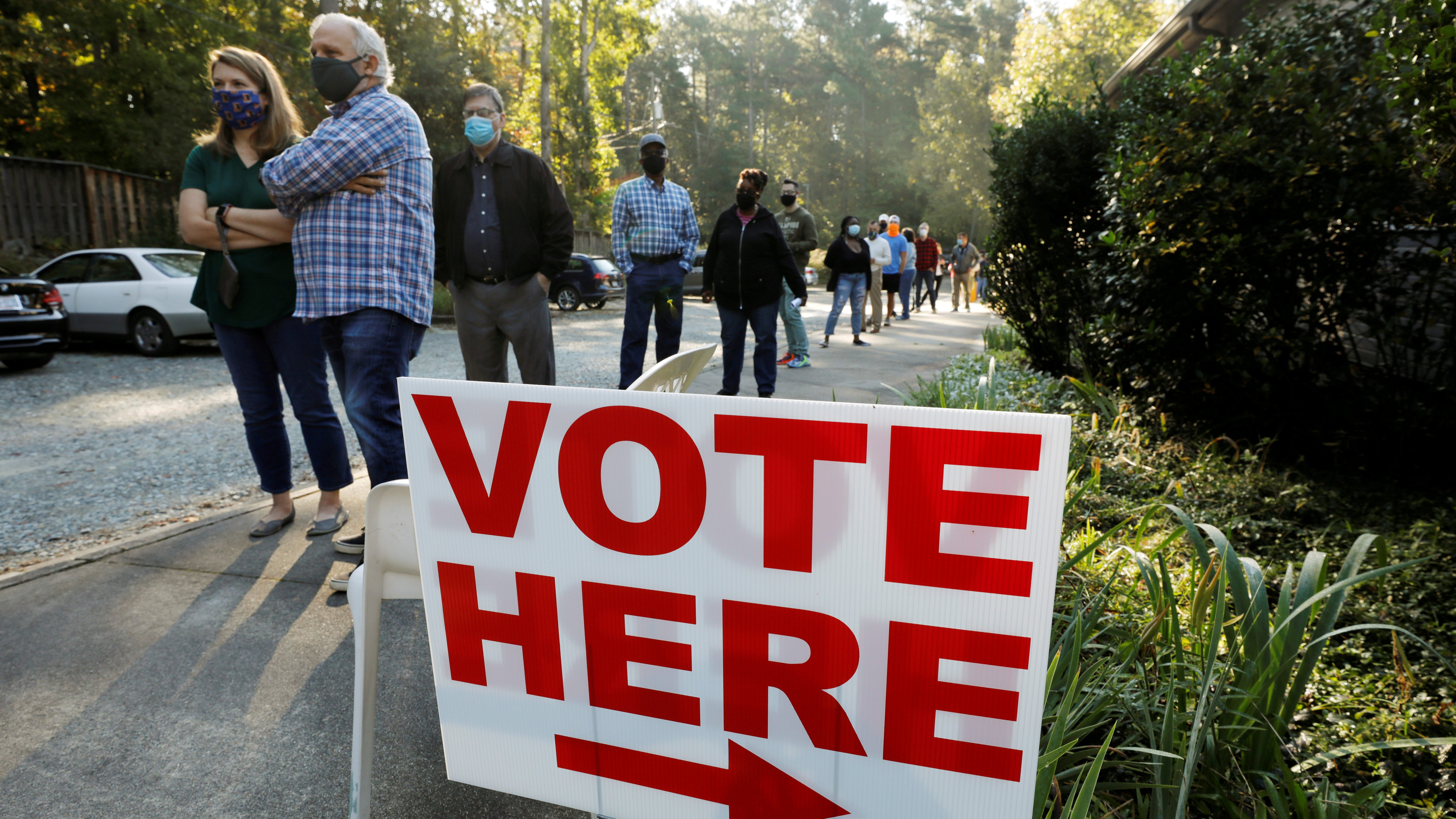 """Voters wait in line by a """"vote here"""" sign"""