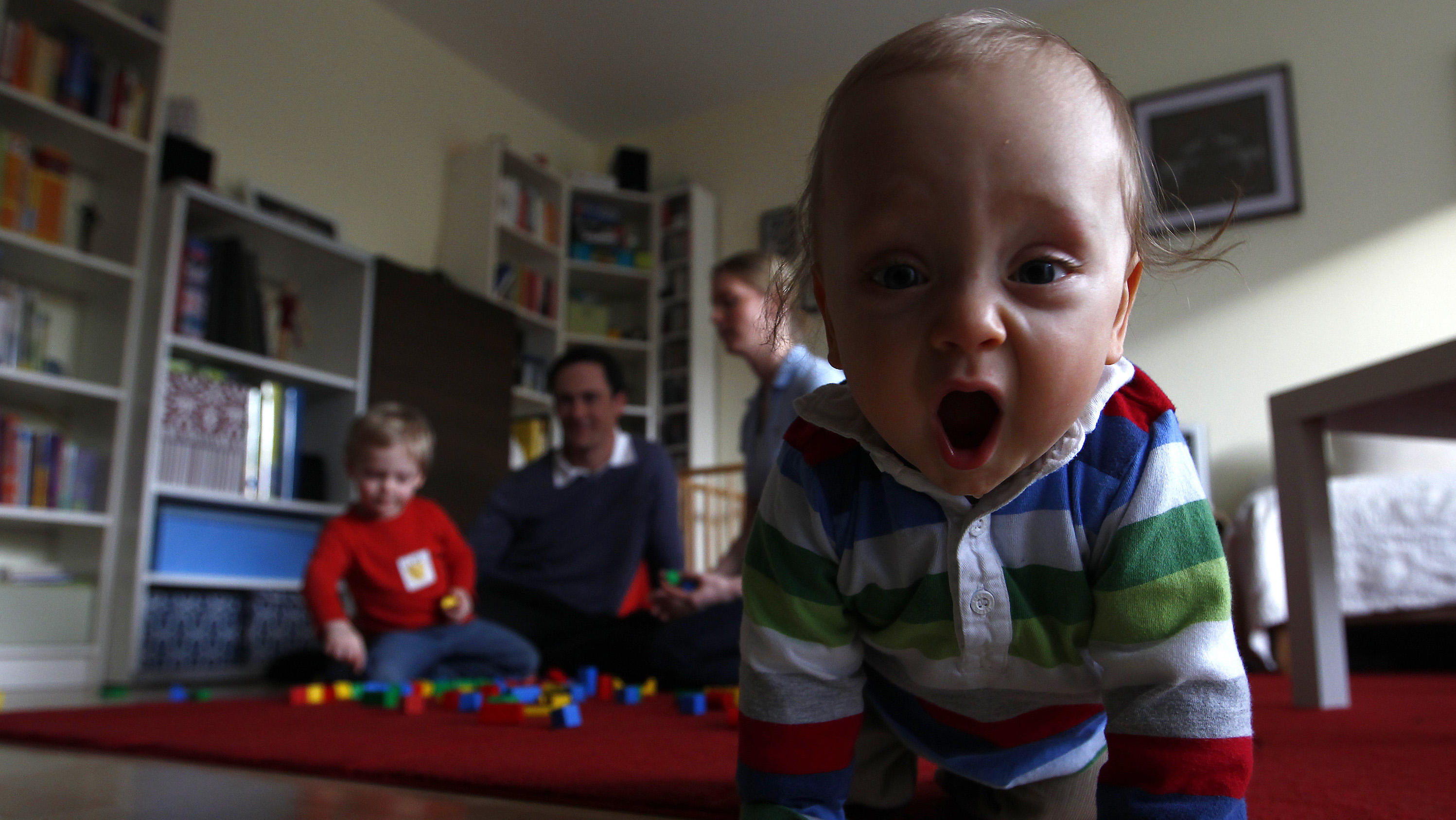 a baby crawls toward the camera with parents in the background