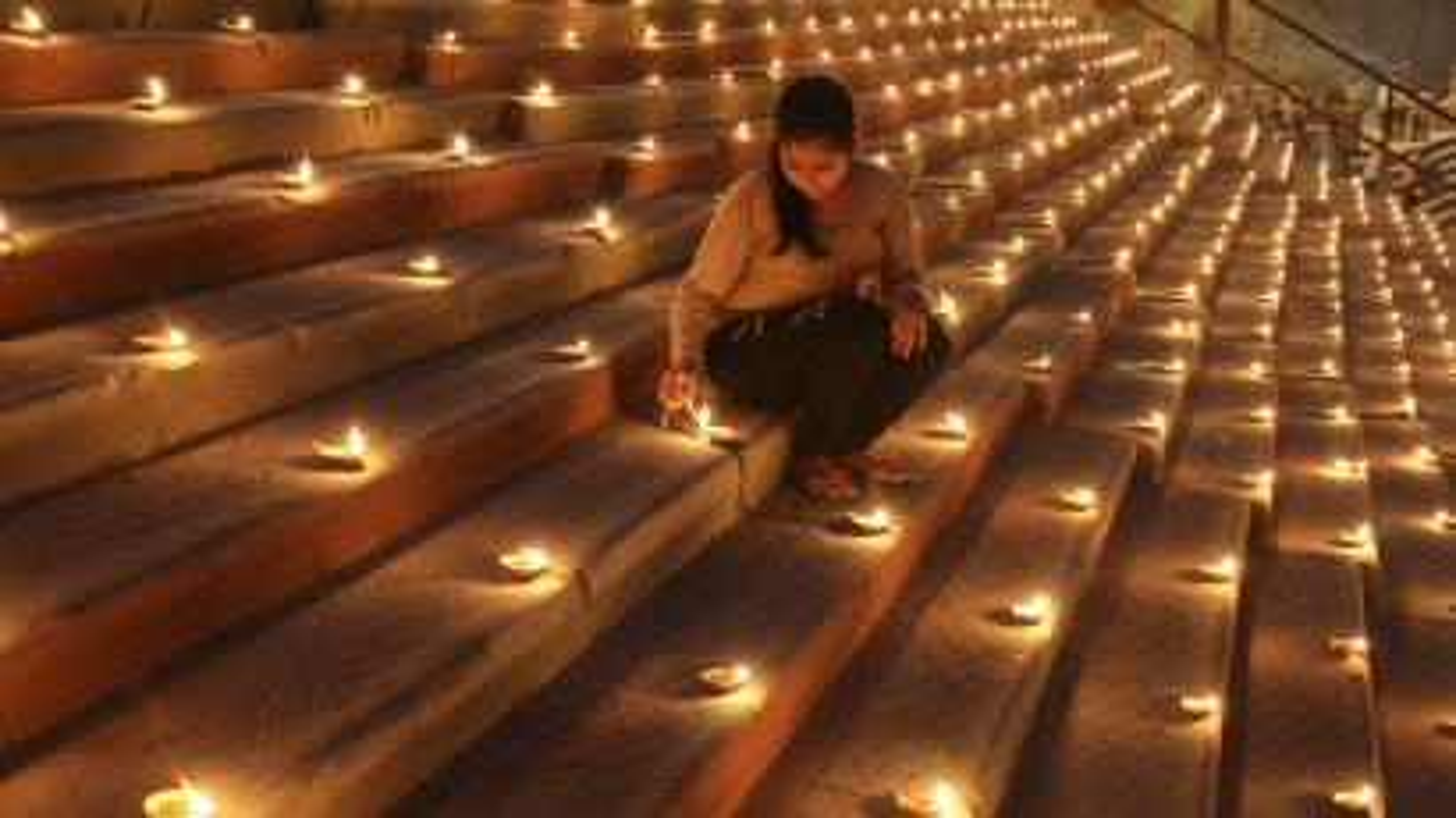 A Hindu devotee lights an earthen lamp on the steps of Sindhiya Ghat during the Karthik Purnima and Dev Diwali festival in Varanasi