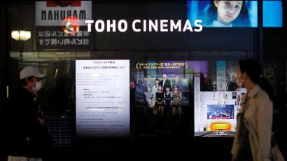 Passersby wearing protective face masks walk past notices of closed and business hours reduction displayed in front of a movie theater in Tokyo