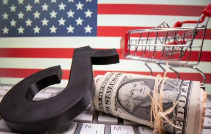 A 3D printed Tik Tok logo, dollar banknotes, shopping cart and keyboard are seen in front of U.S. flag