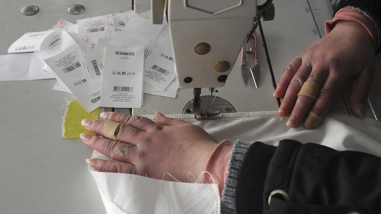An employee sews a piece of cloth at a garment factory