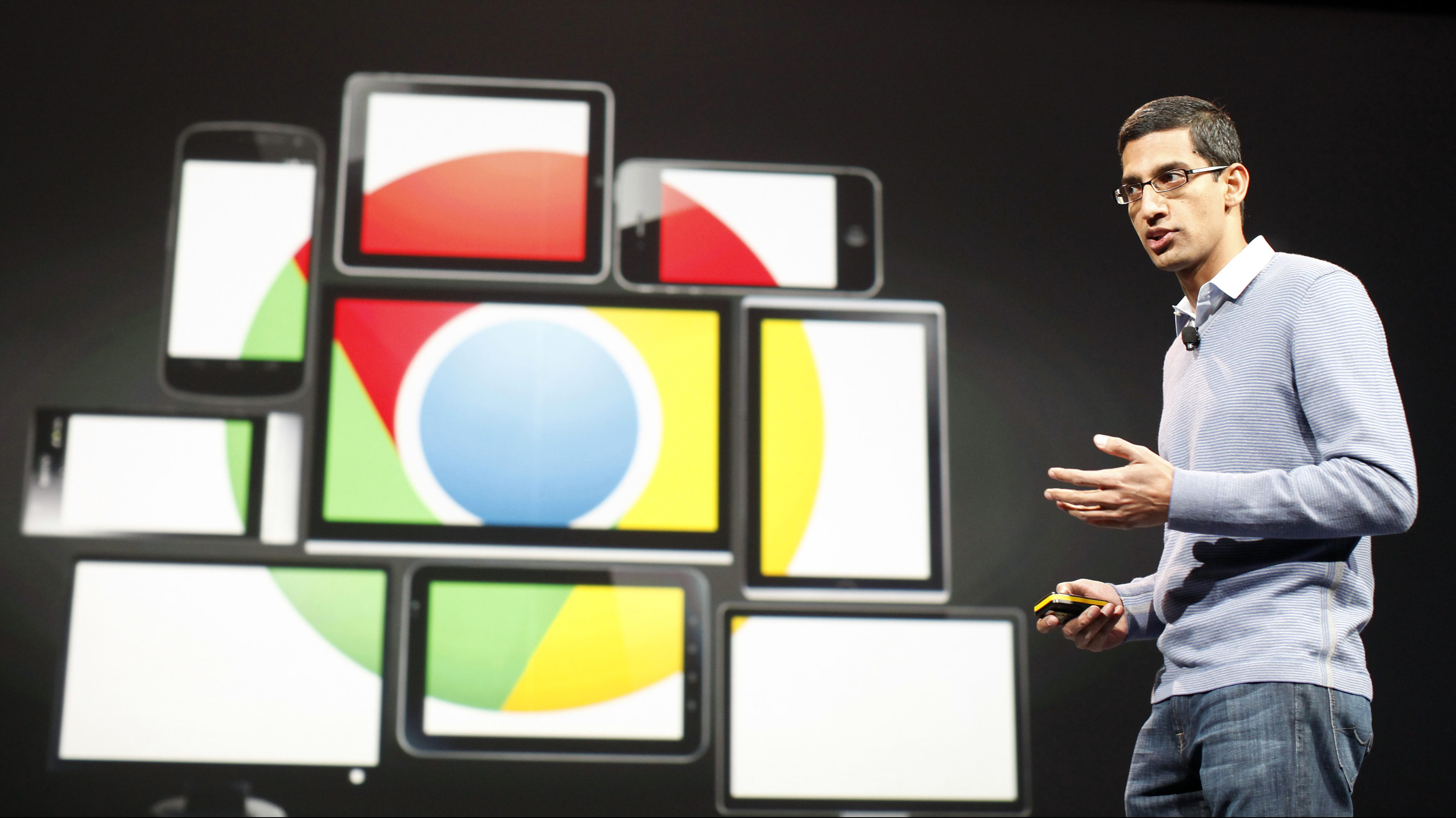 Sundar Pichai stands in front of a group of screens displaying the Google Chrome logo.