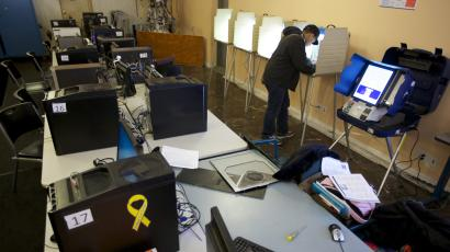 A man fills out a ballot at a booth inside an internet cafe, behind a row of computers.