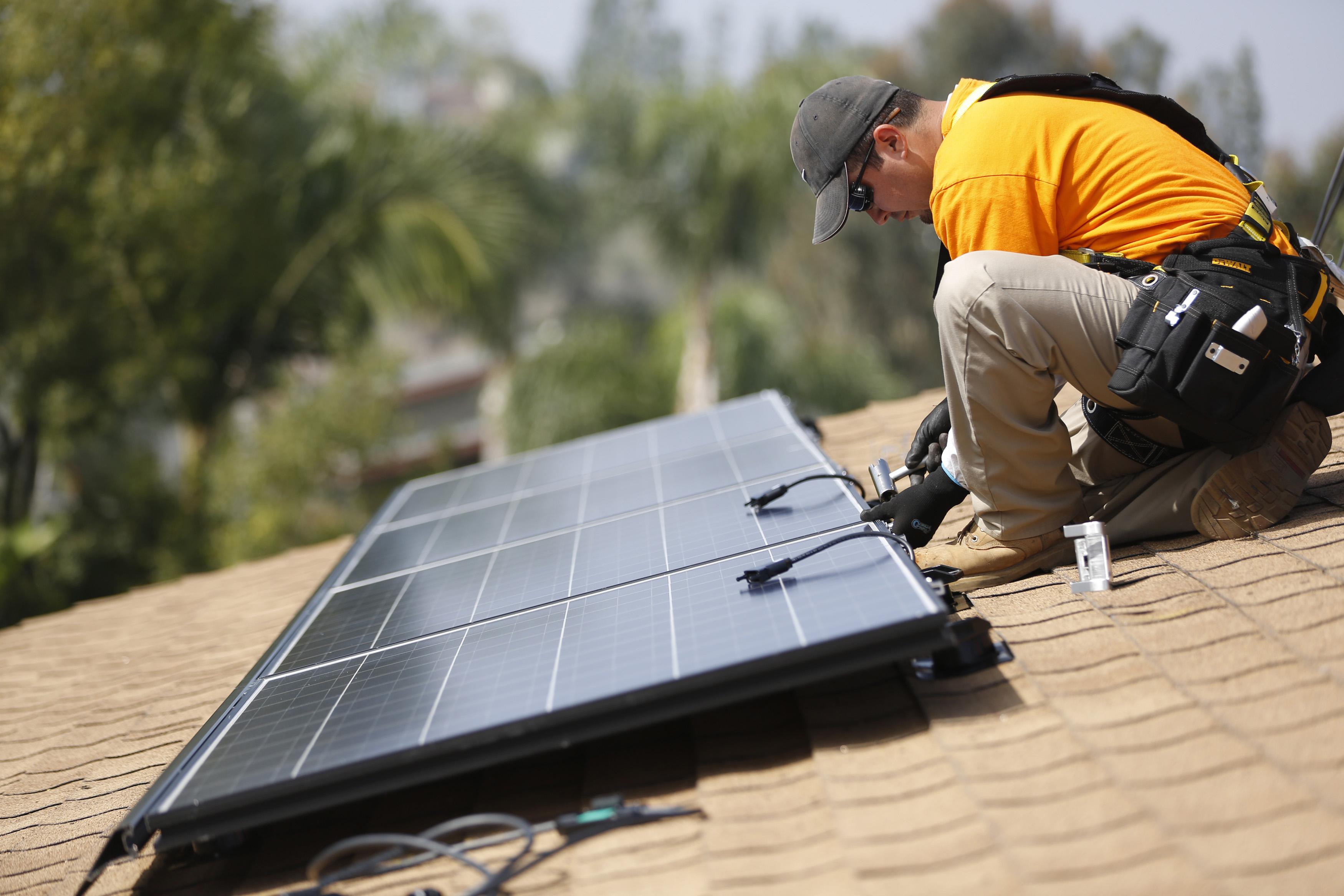 Vivint Solar technician Eduardo Aguilar installs solar panels on the roof of a house in Mission Viejo, California October 25, 2013.