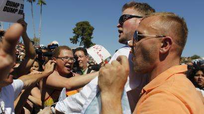 Sunglasses and collar wearing Trump supporters argue with anti-Trump protesters at a rally under a clear blue sky in Arizona.