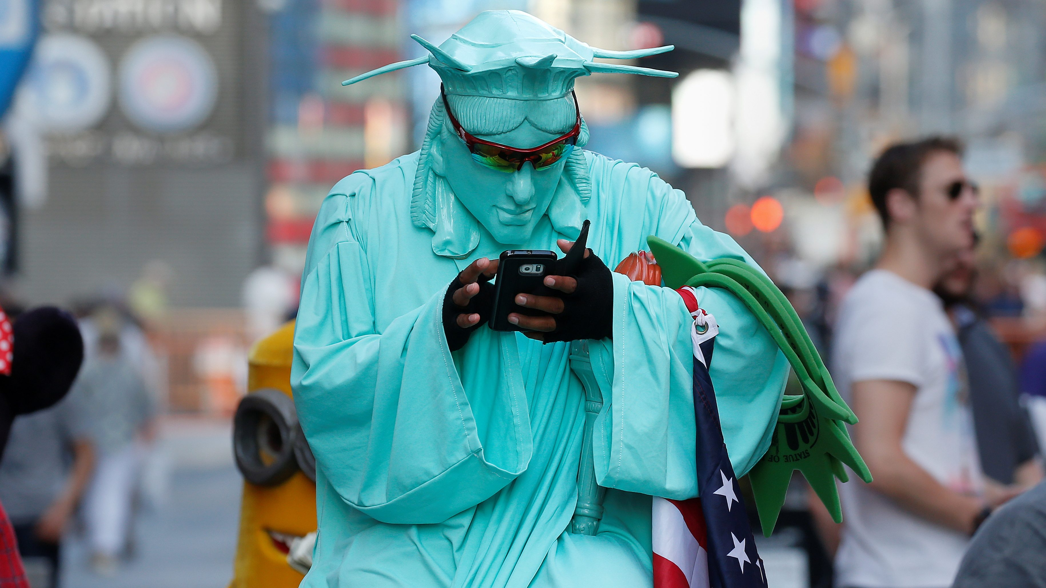 A person wearing a Statue of Liberty outfit to pose for tips checks his cell phone during warm weather in Times Square in the Manhattan borough of New York, New York, U.S., October 19, 2016.