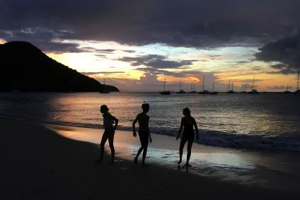Youths play in the water on the beach of Rodney Bay after sunset in Gros Islet, St. Lucia, November 23, 2016.