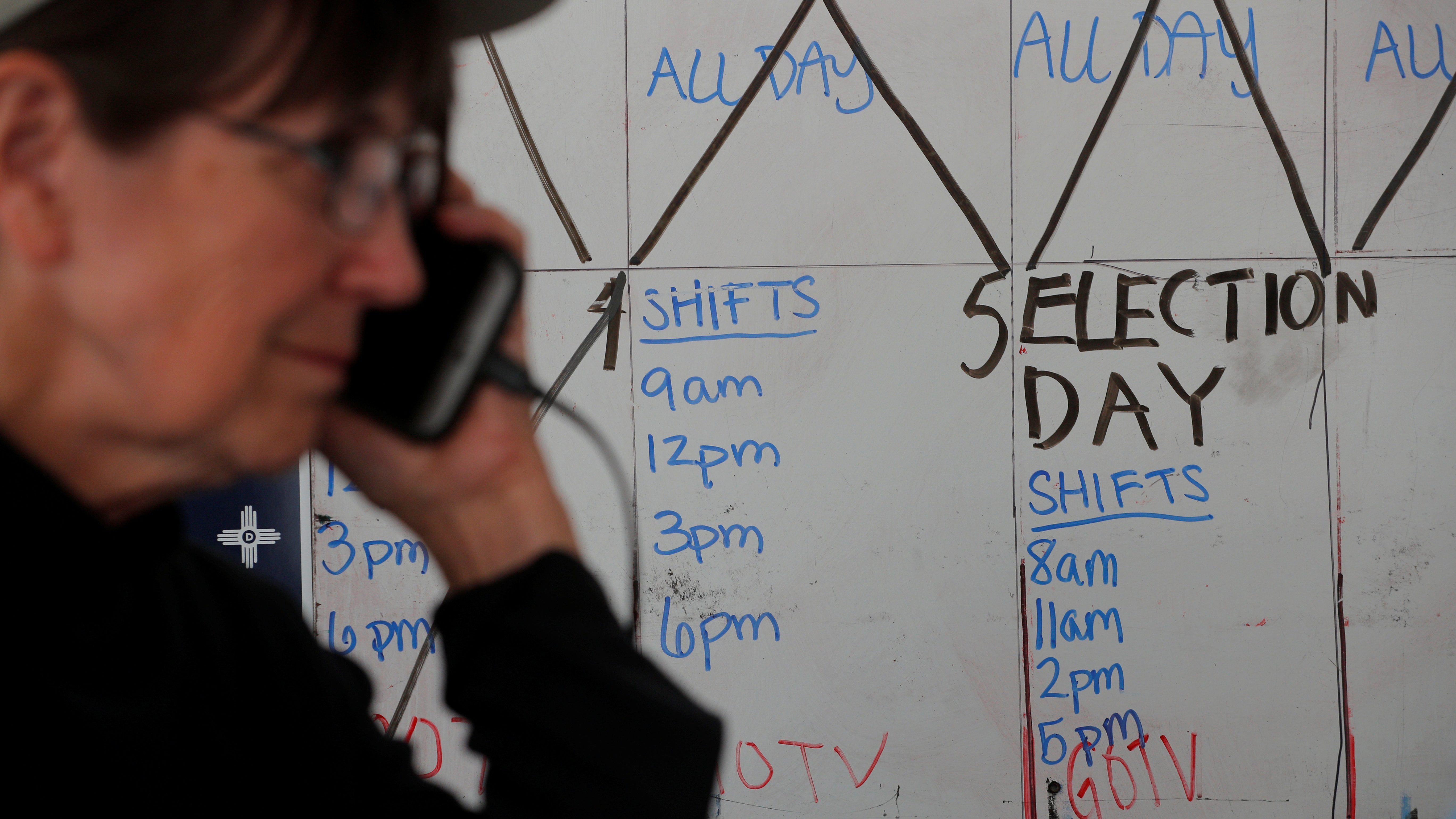 A volunteer makes phone bank calls to voters in front of an election countdown calendar at a Democratic Party office in Albuquerque, New Mexico, U.S., November 5, 2018.