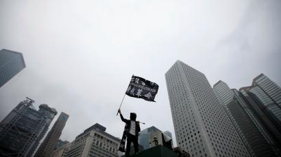 An anti-government protester waves a flag during a rally at Edinburgh Place in Hong Kong