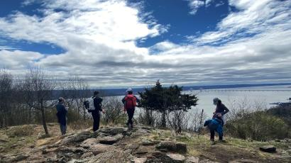 Hikers practice social distancing as they stand on a trail above the Hudson River in Hook Mountain State Park