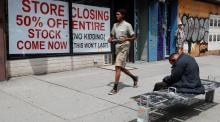A man walks past a store closing advertisement while a person sits on a bench with his head down in New York City.