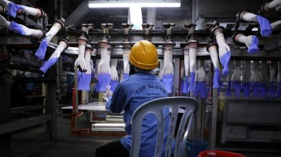 A worker inspects newly-made gloves at Top Glove factory in Shah Alam, Malaysia