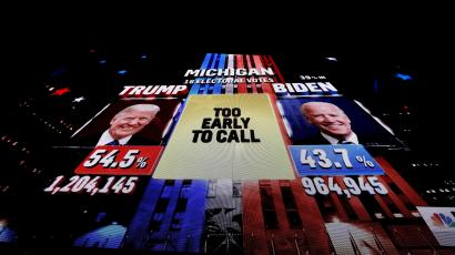 A giant television screen shows a network TV broadcast showing the U.S. presidential race
