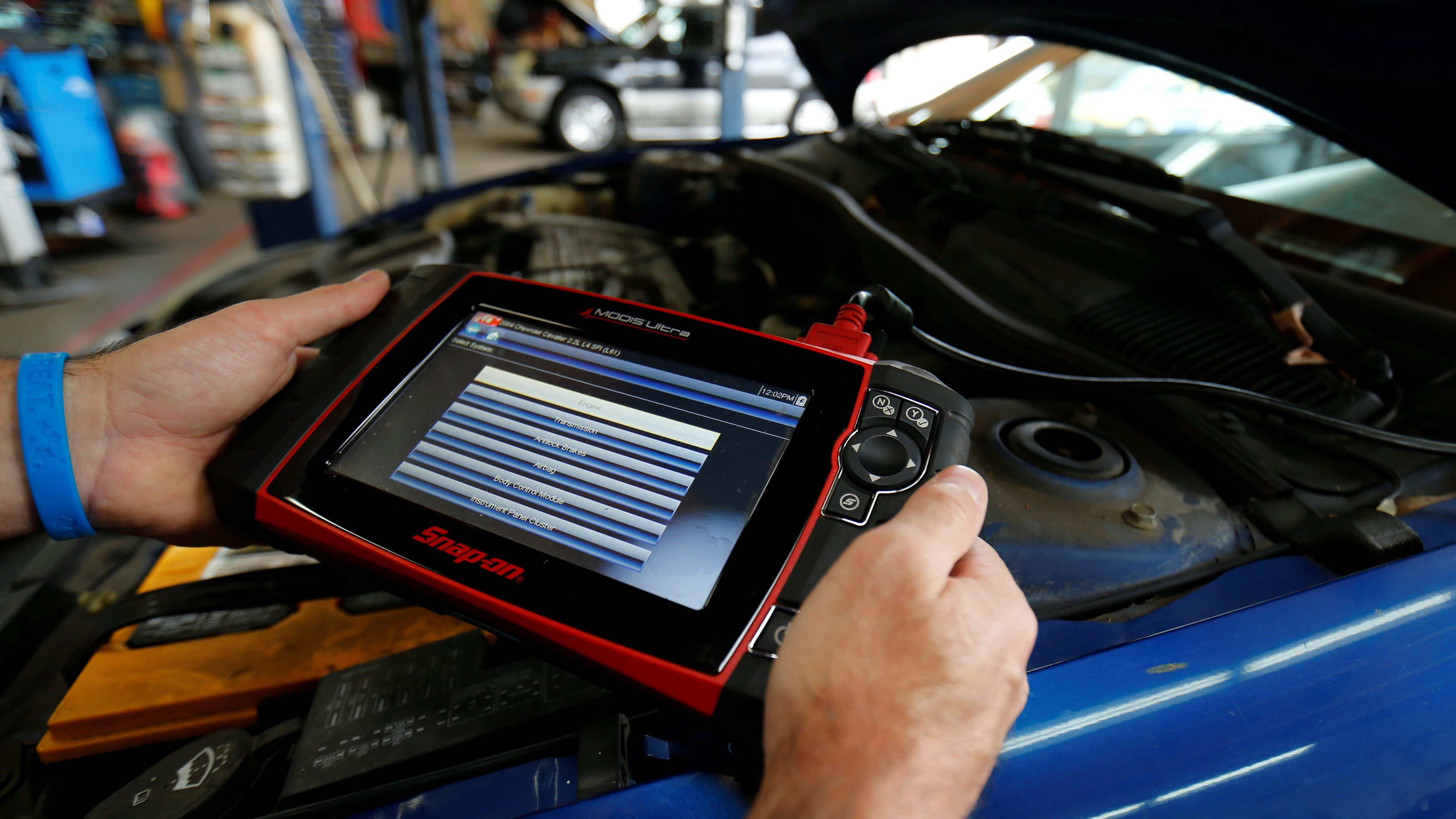 A mechanic holds an iPad displaying data from a car's computer while it sits in the background with its hood popped open.