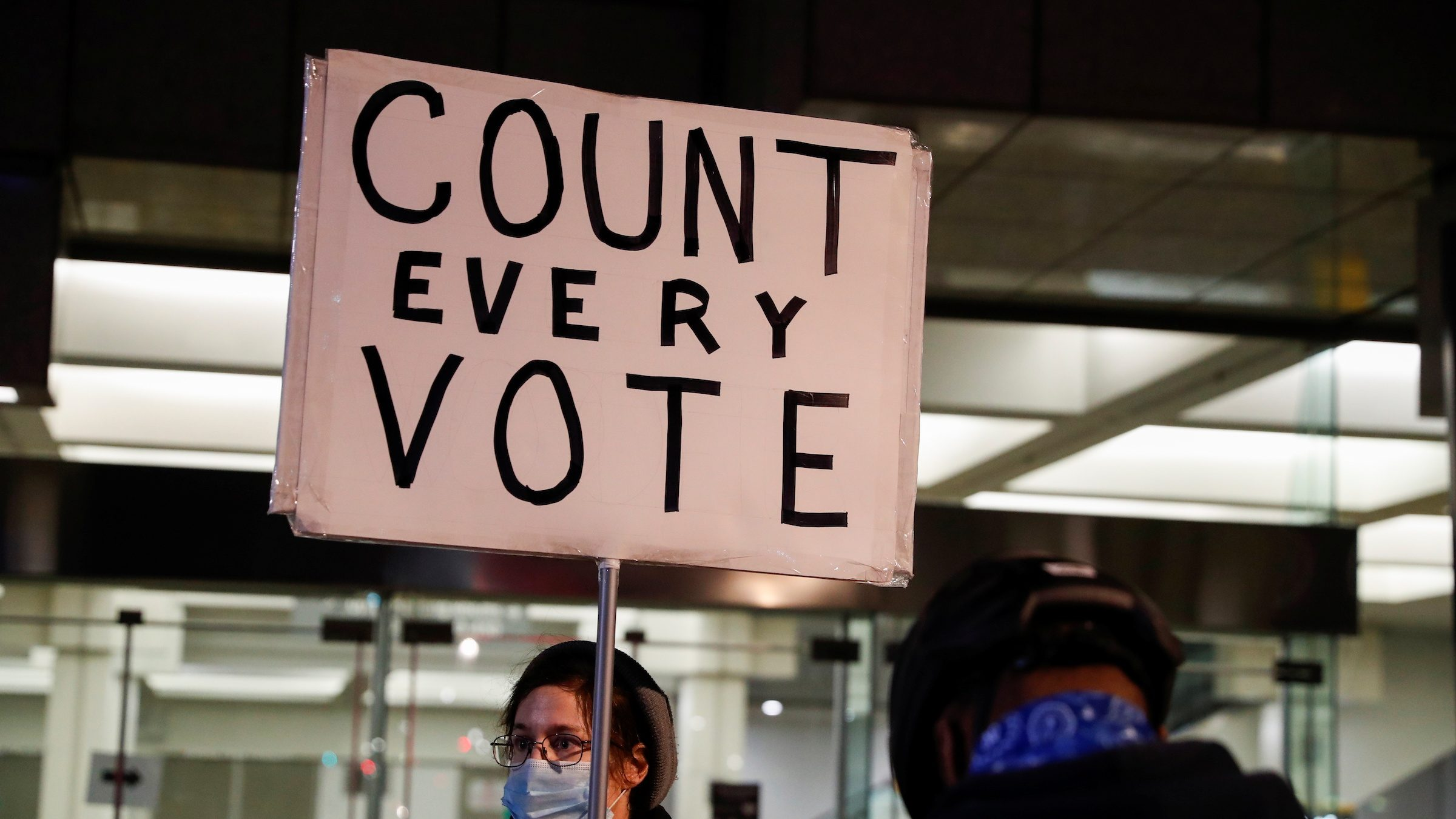 "A person holds a sign reading ""count every vote"""