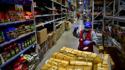 An employee restocks shelves with packs of firewood at a Lowe's hardware store.