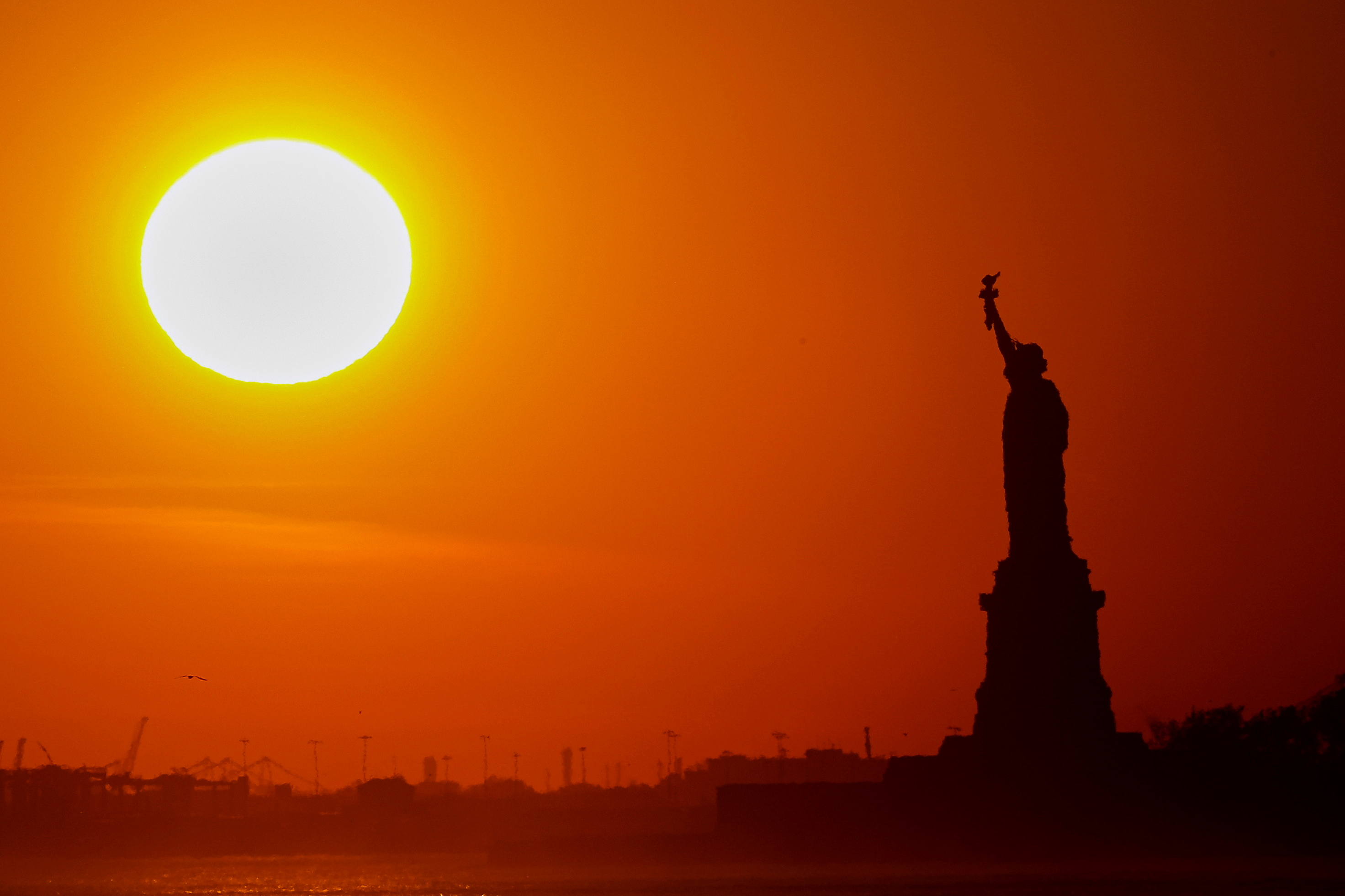 The Statue of Liberty is seen at sunset in New York Harbor
