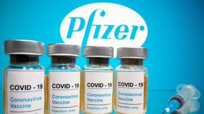 "Vials with a sticker reading, ""COVID-19 / Coronavirus vaccine / Injection only"" and a medical syringe are seen in front of a displayed Pfizer logo in this illustration taken October 31, 2020."