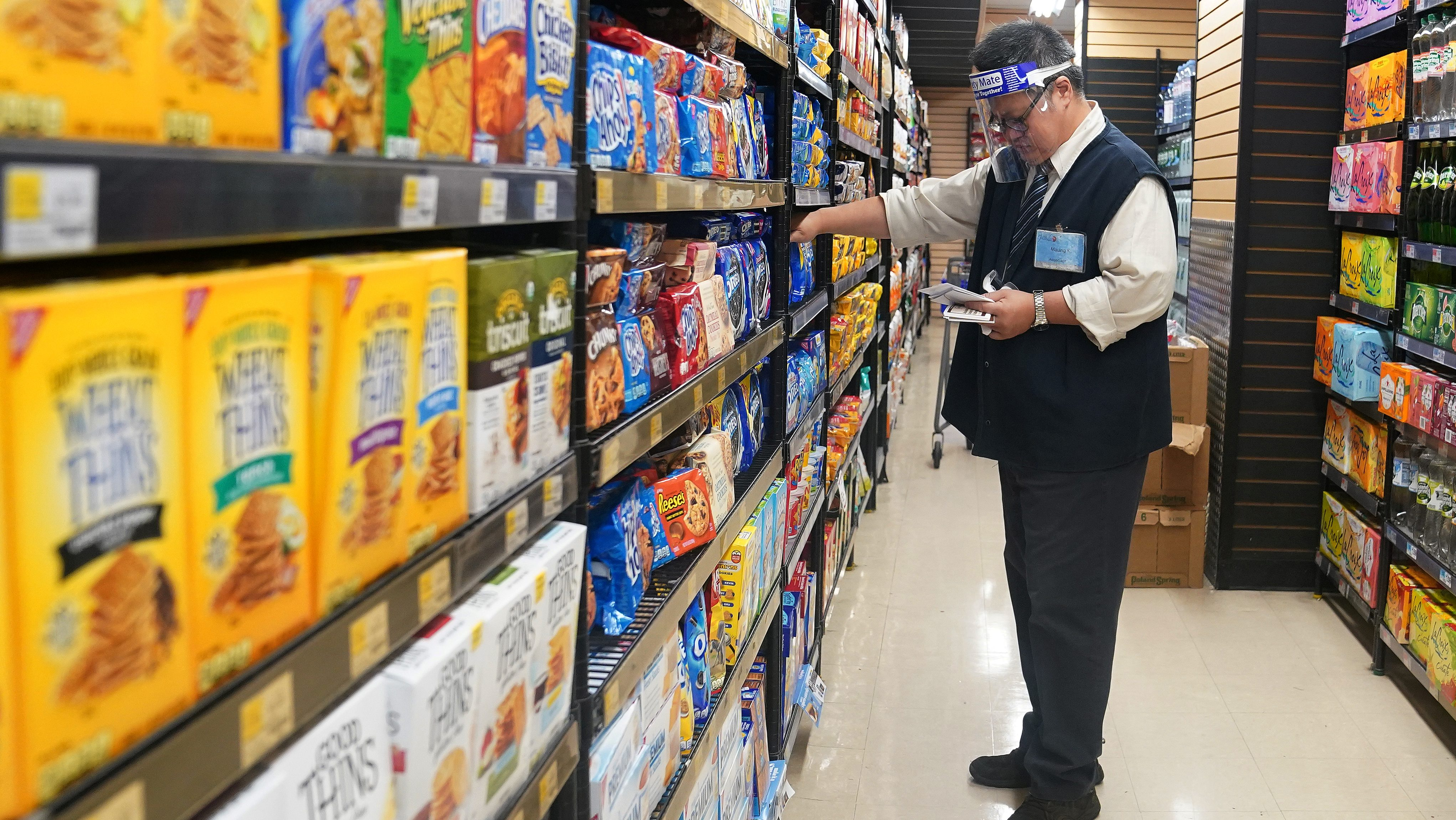 A worker with a face shield checks products on the shelf of a grocery store in the Manhattan borough of New York City, New York, U.S., August 7, 2020.