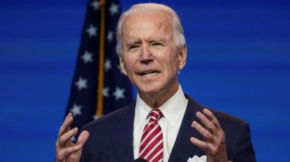 US President-elect Joe Biden stands in front of a blue background and US flag with his hands in front of his chest while speaking.