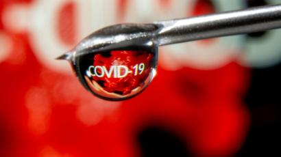 """The word """"COVID-19"""" is reflected in a drop on a syringe needle in this illustration taken November 9, 2020."""