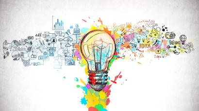 Creative and colorful light bulb sketch and business plan icons drawn on concrete wall.
