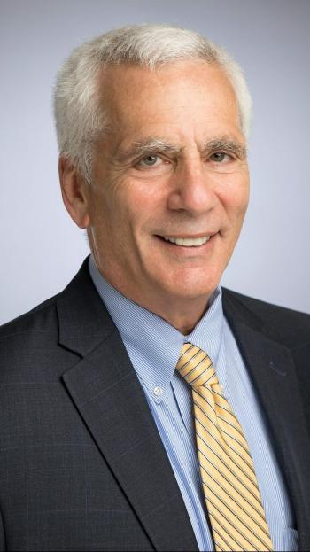 Jared Bernstein stands smiling in front of a grey background wearing a dark grey jacket, yellow striped tie, and light blue shirt.