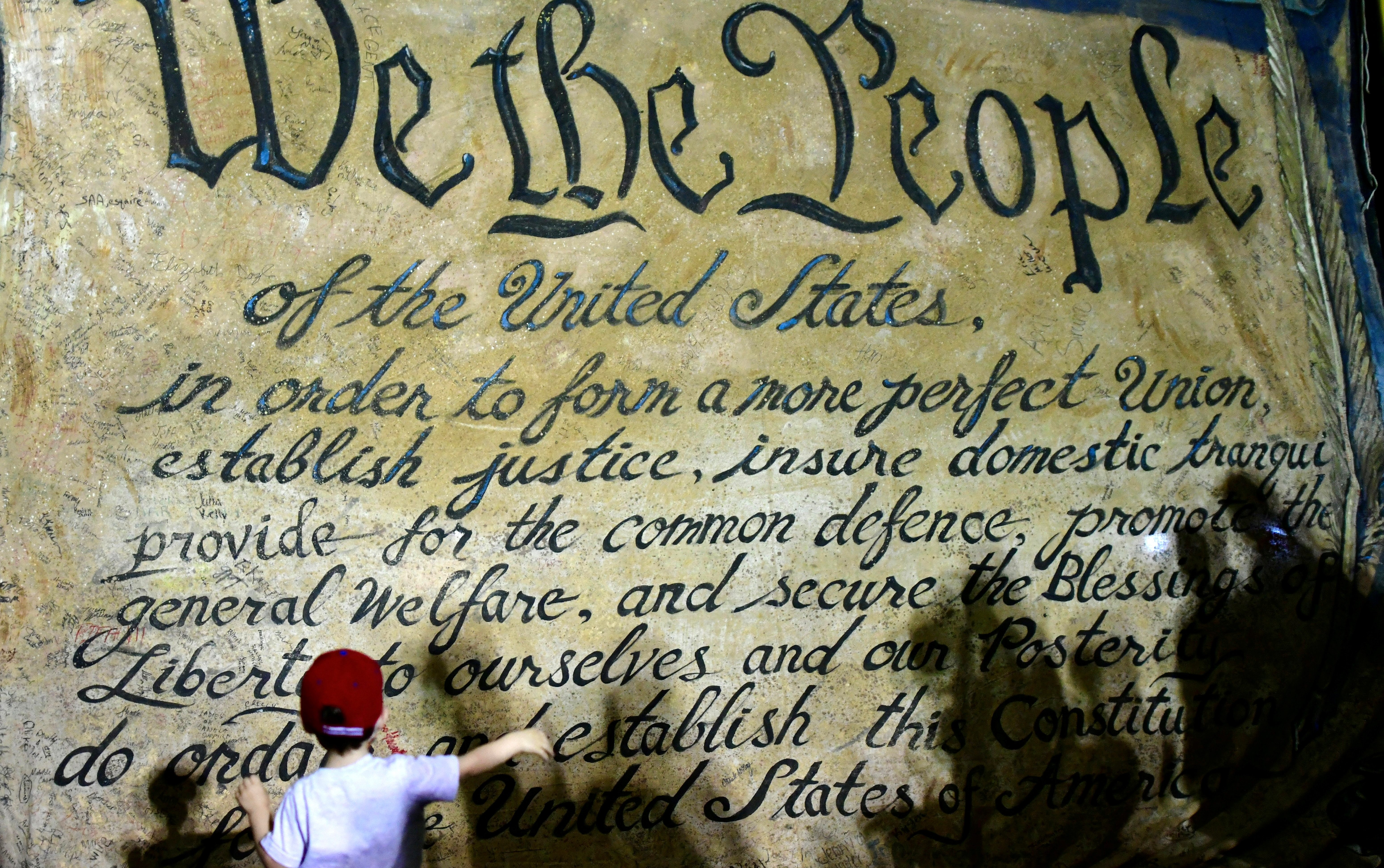 """A child runs toward a U.S. constitution banner stating """"We the People"""" after the 2020 U.S. presidential election,"""