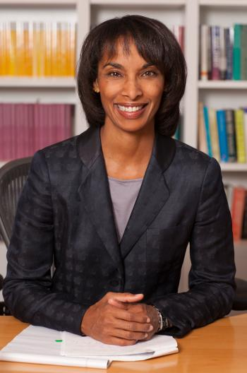 Labor economist and Princeton dean Cecilia Rouse smiles and sits at at desk in front of bookcases in a black blazer.