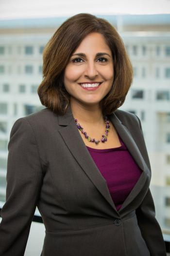 Neera Tanden of the Center for American Progress smiles and stands in front of a window wearing a grey blazer, dark purple top and a necklace.