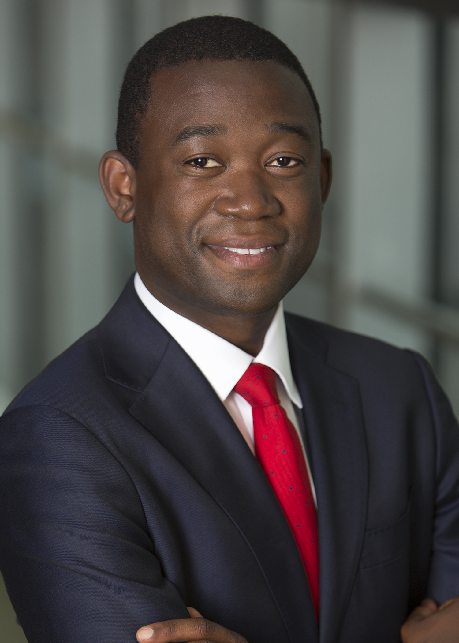 """Adewale """"Wally"""" Adeyemo smiles at the camera with his arms across his chest while wearing a dark blue jacket, white dress shirt and red tie."""