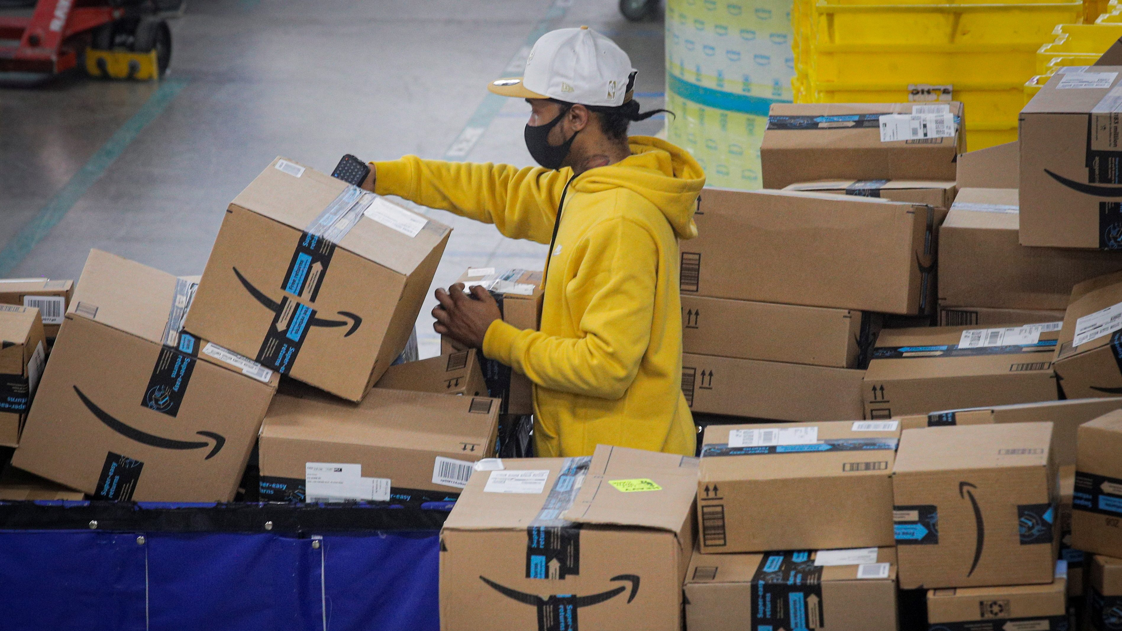 An employee scans packages at Amazon's JFK8 distribution center in Staten Island, New York, U.S. November 25, 2020.