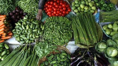 Vendor arranges vegetables at wholesale market in Siliguri