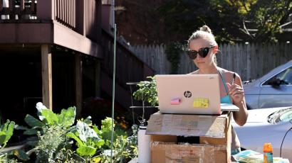 A woman working from home because of the coronavirus disease (COVID-19) pandemic, sunbathes as she works at a standing desk she fashioned from a gardening table in Washington, U.S.