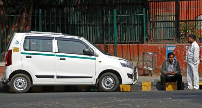Uber and Ola drivers sit next to their parked vehicle's during a protest in New Delhi