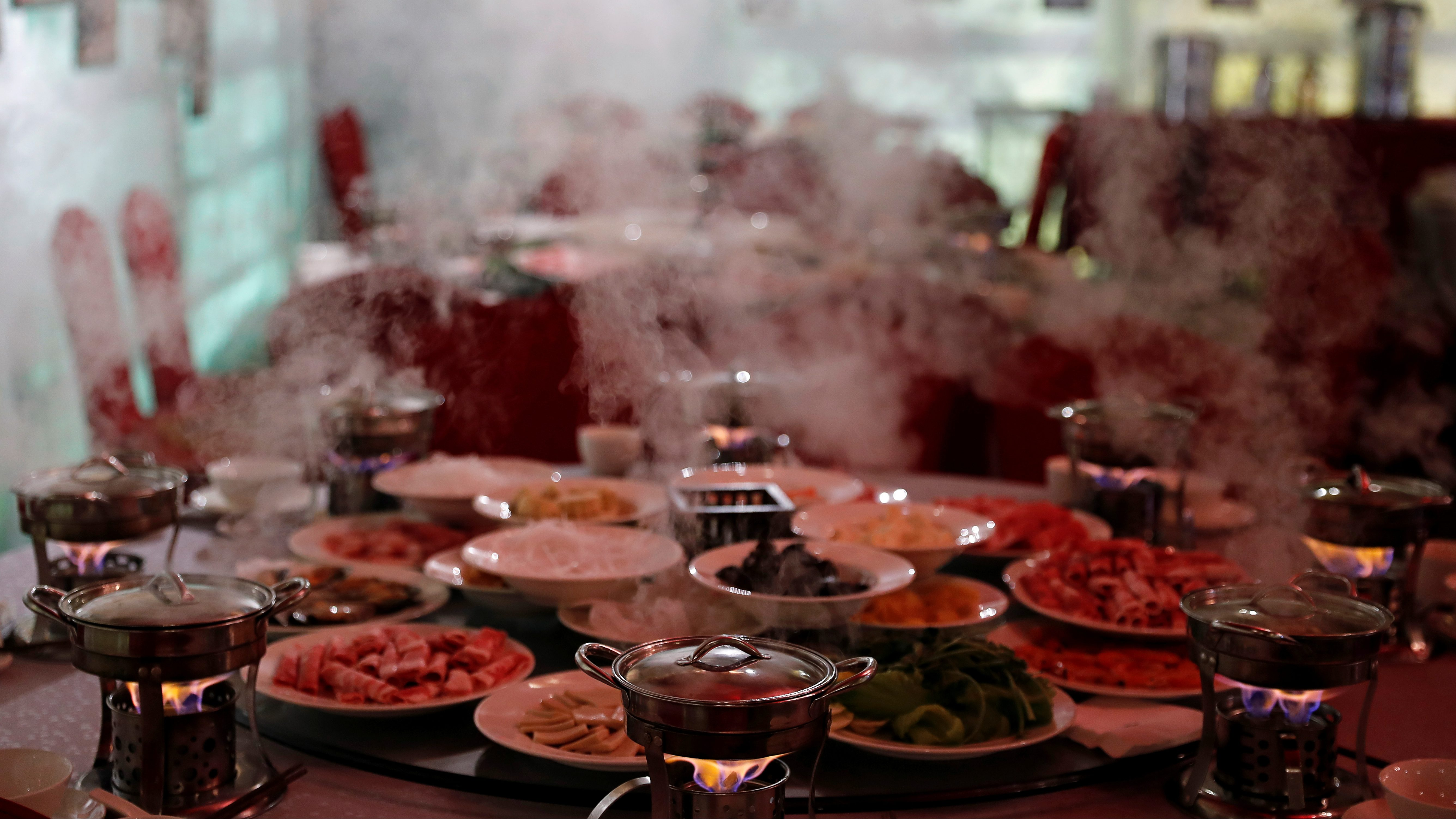 """Hot steam rises from hotpots at Shangri-La Hotel's """"Ice Palace"""" restaurant and bar in Harbin"""