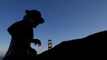 A person running in front of the Golden Gate Bridge in San Francisco; a shadow covers their face.