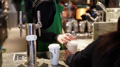 Starbucks barista in London hands a cup to a customer