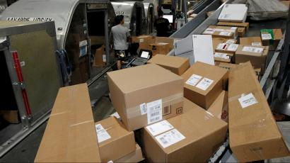 United Parcel Service employees load packages at the UPS Worldport International Hub in Louisville, Kentucky