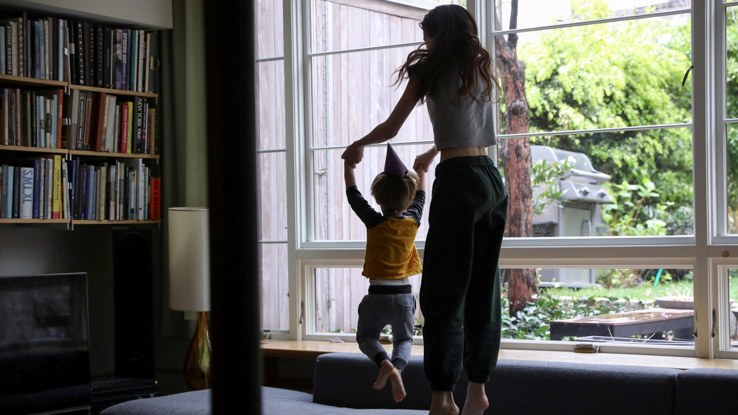 A woman wearing a grey t-shirt and black sweatpants jumps on a blue L-shaped couch with a young boy wearing a paper cone birthday hat. His hands are holding hers and they are both jumping in the air facing a large window. A wooden shed and grill is visible in the yard.