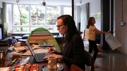 A woman wearing glasses juggles work and childcare responsibilities. She sits at a table covered in paint pallets, papers, two mugs, and other items, trying to work on a laptop in a large multifunction room. A young girl plays in the background on the right and a young boy can be seen on the left in front of a couch. A colorful striped play tent can be seen in the background in front of a large window.