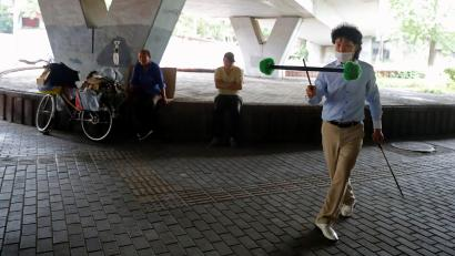 A man wearing a protective mask juggles a devil stick after a new outbreak of the coronavirus disease (COVID-19) in Beijing, China, June 26, 2020.