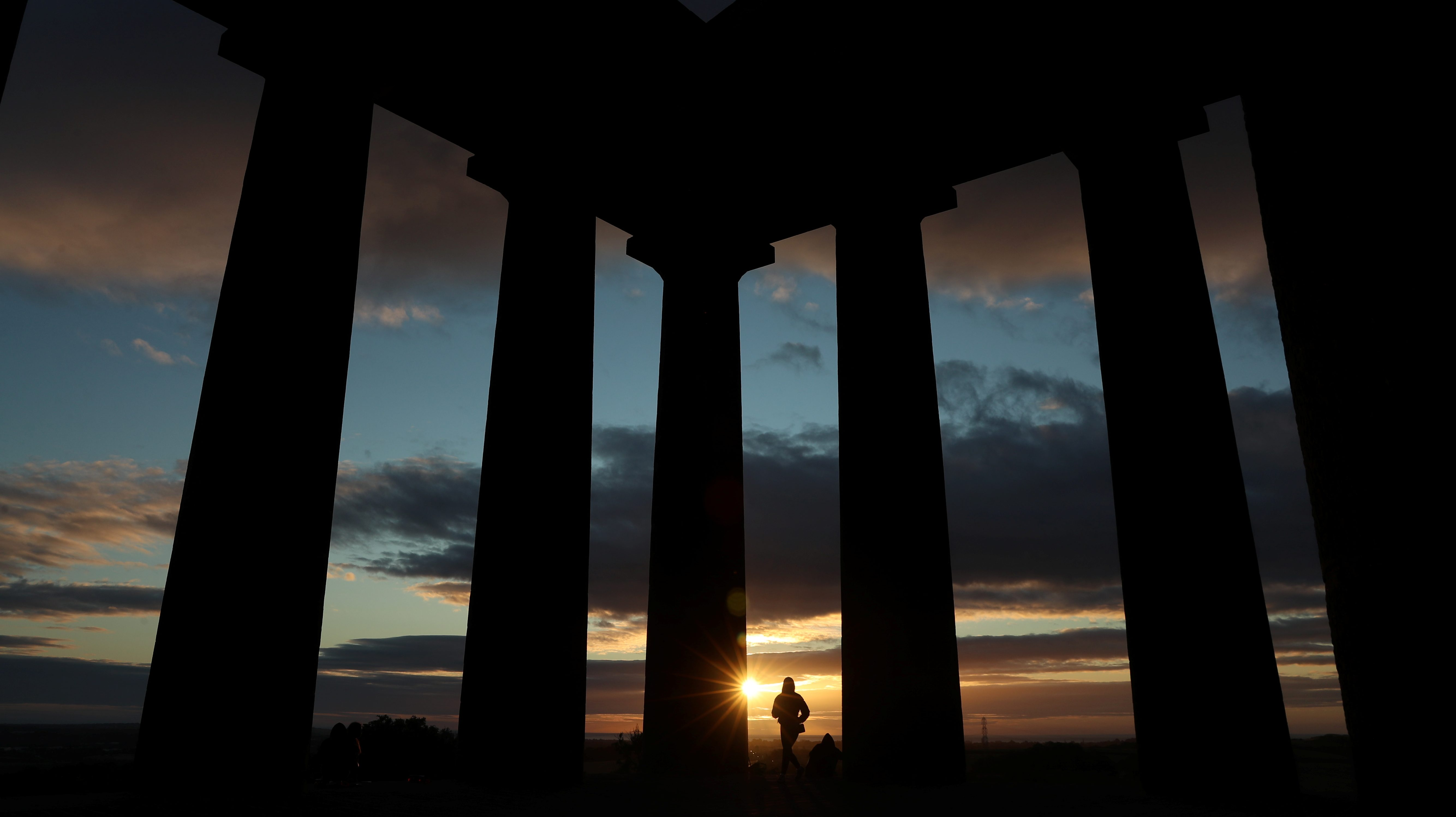 People watch the sunrise from Penshaw Monument, County Durham, Britain